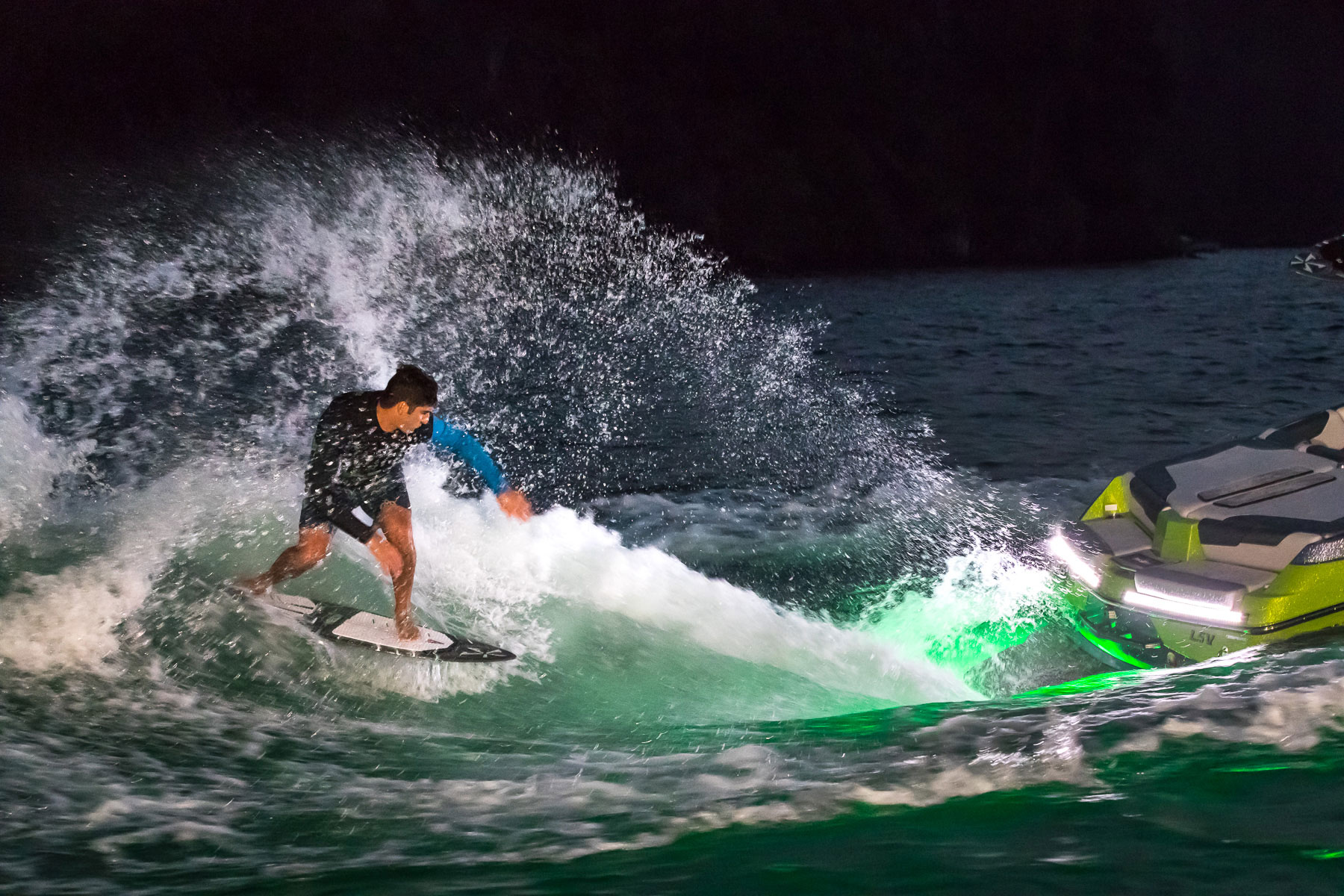 Wake surfer at night with underwater LED lights