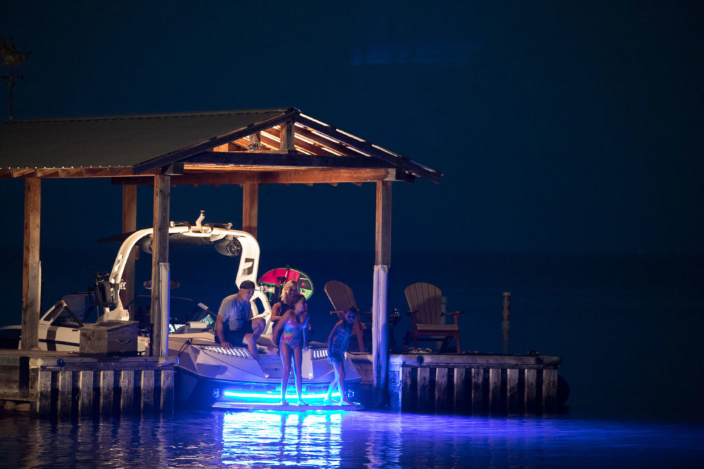 A family enjoys boating at night with blue underwater LED lights